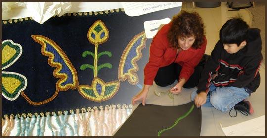 Sherri is showing Bryce how to use pastels to draw Common Yarrow. (Glenbow Museum. (2005). Nitsitapiisinni Exhibit. Calgary, Alberta: Blackfoot Gallery Committee.)