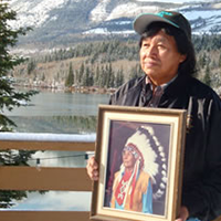 Dale House is seen here holding a photo of his father which you will see hanging on the wall at Nakoda Lodge.